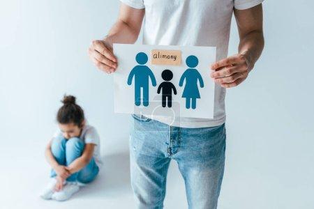 foyer sélectif du père tenant le papier avec la famille dessinée et le lettrage de pension alimentaire près bouleversé gamin afro-américain sur blanc