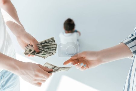 selective focus of man giving alimony to woman near daughter on white