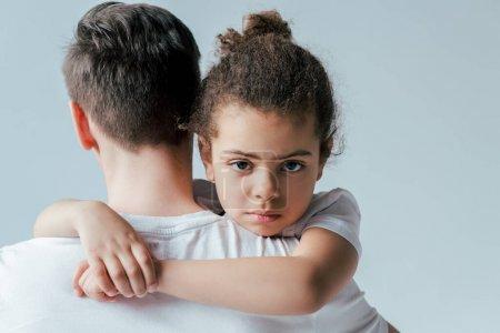arrière vue du père adoptif emporter bouleversé afro-américaine fille isolée sur blanc, concept de garde