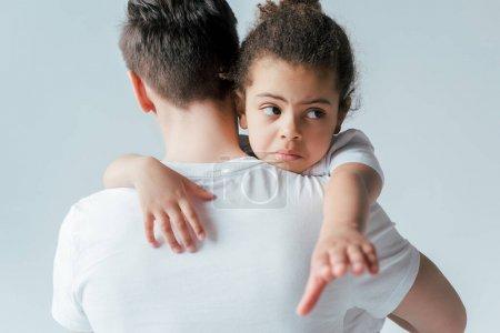 vue arrière du père adoptif emmenant triste fille afro-américaine isolée sur blanc, concept de garde