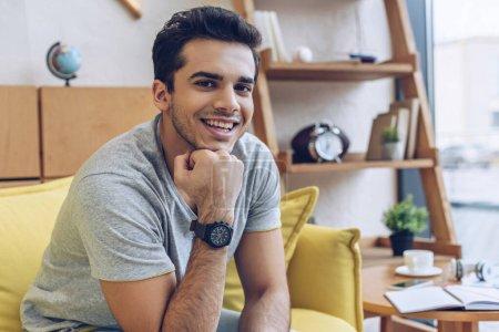 Mann lächelt und blickt auf Sofa im Wohnzimmer in die Kamera