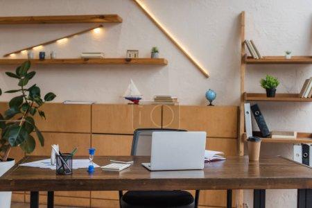 Photo pour Table avec ordinateur portable, sablier et porte-stylo au bureau - image libre de droit