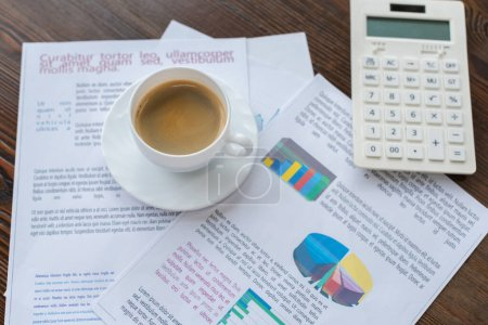 Selective focus of cup of coffee on papers near calculator on table