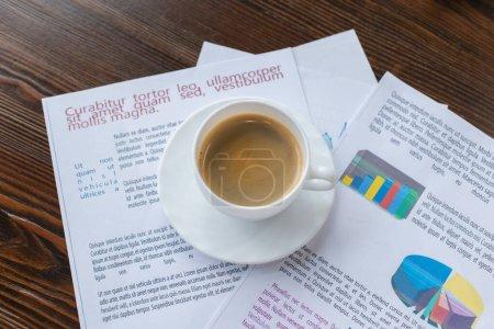 Photo pour Vue à grand angle d'une tasse de café sur du papier sur une table - image libre de droit