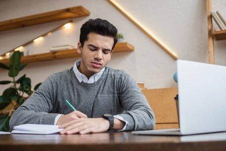 Photo pour Vue à angle bas de l'homme d'affaires écrivant avec crayon dans un ordinateur portable près d'un ordinateur portable à la table - image libre de droit