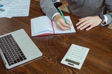 Photo pour Vue recadrée de l'homme d'affaires écrivant dans un carnet près d'un ordinateur portable, une calculatrice et des papiers à table au bureau - image libre de droit