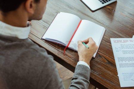 Photo pour Vue recadrée de l'homme d'affaires écrivant dans un cahier à la table au bureau - image libre de droit