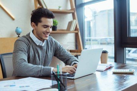 Photo pour Orientation sélective de l'homme d'affaires souriant et travaillant avec ordinateur portable à table dans le bureau - image libre de droit