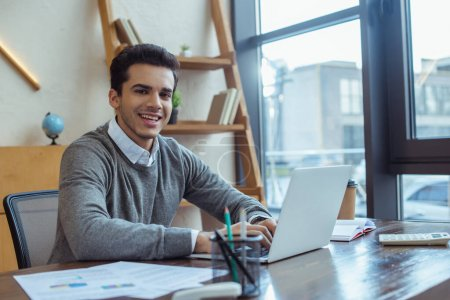 Photo pour Concentration sélective de l'homme d'affaires travaillant avec un ordinateur portable, souriant et regardant la caméra à la table dans le bureau - image libre de droit