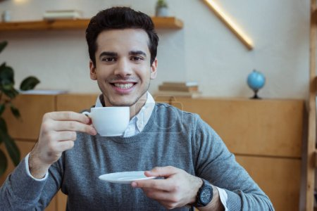 Photo for Businessman holding saucer and cup of coffee, smiling and looking at camera in office - Royalty Free Image