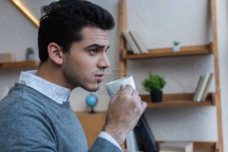 Nachdenklicher Geschäftsmann mit Tasse Kaffee im Büro
