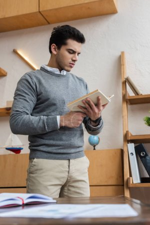 Photo pour Vue en angle bas du livre de lecture d'homme d'affaires dans le bureau - image libre de droit