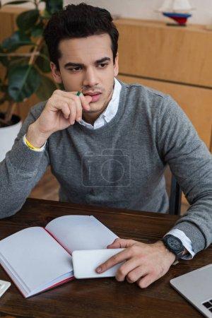 Photo pour Homme d'affaires réfléchi avec smartphone et crayon près du carnet à table - image libre de droit