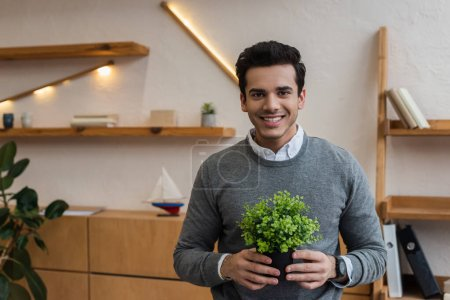 Front view of businessman with flowerpot smiling and looking at camera in office
