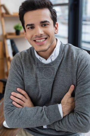 Photo pour Homme d'affaires avec bras croisés regardant la caméra et souriant - image libre de droit