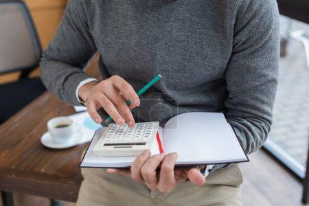 Photo pour Vue recadrée de l'homme d'affaires avec crayon et ordinateur portable à l'aide de la calculatrice dans le bureau - image libre de droit