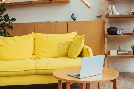 Photo pour Café avec ordinateur portable près du canapé dans le salon - image libre de droit