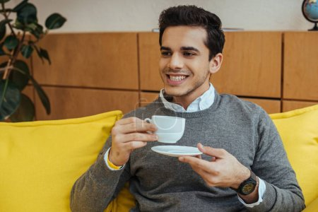 Photo for Man smiling and holding saucer and cup of coffee on sofa - Royalty Free Image