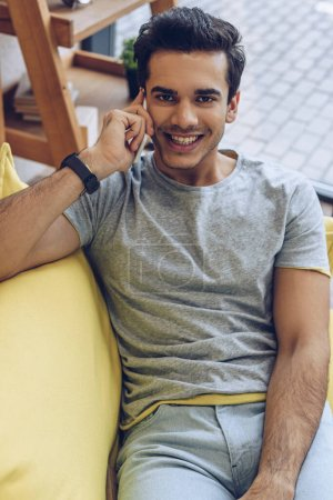 High angle view of man talking on smartphone, looking at camera and smiling on sofa