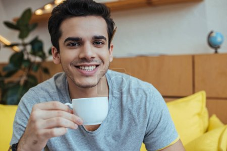 Man with cup of coffee smiling and looking at camera