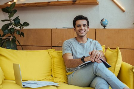 Photo pour Freelance avec ordinateur portable près de portable avec des papiers souriant et regardant la caméra sur le canapé dans le salon - image libre de droit