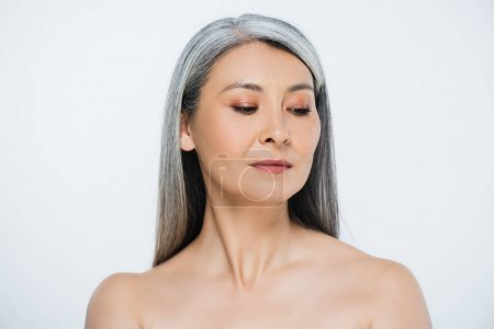 attractive adult asian naked woman with perfect skin and grey hair isolated on grey