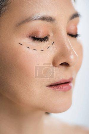 Photo pour Asiatique femme avec fermé les yeux et plastique chirurgie lignes sur visage isolé sur gris - image libre de droit