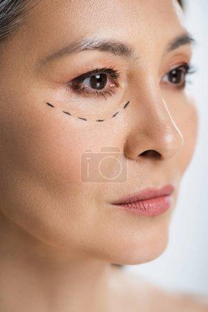 Photo pour Asiatique femme avec plastique chirurgie lignes sur visage isolé sur gris - image libre de droit
