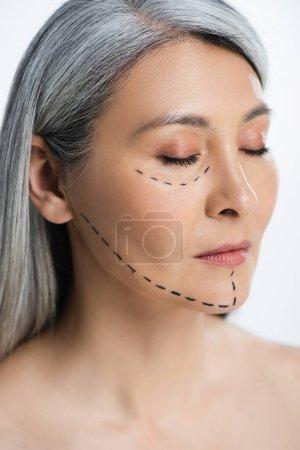 Photo pour Asiatique femme avec les yeux fermés et la chirurgie plastique correction marque sur visage isolé sur gris - image libre de droit