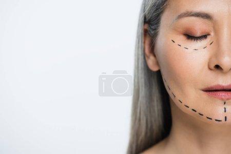 Photo pour Demi-vue du visage de la femme asiatique avec des lignes de chirurgie plastique isolé sur gris - image libre de droit