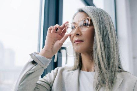 Photo pour Femme d'affaires asiatique réfléchie avec des cheveux gris en costume gris et des lunettes au bureau - image libre de droit