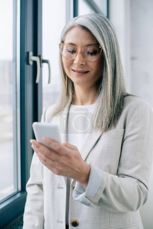 adult smiling asian businesswoman in eyeglasses with grey hair using smartphone in office