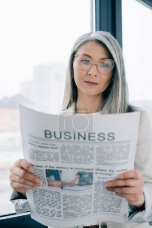 Photo for Confident asian businesswoman reading business newspaper in office - Royalty Free Image