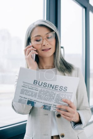 attractive asian businesswoman in eyeglasses talking on smartphone while reading business newspaper in office