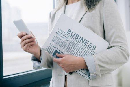Photo pour Vue en rafale d'une femme d'affaires utilisant un téléphone intelligent et tenant un journal d'affaires au bureau - image libre de droit