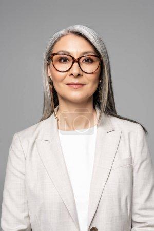 Photo pour Attrayant confiant asiatique femme d'affaires dans lunettes isolé sur gris - image libre de droit