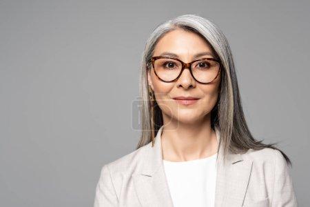 Photo pour Attrayant sourire asiatique femme d'affaires dans des lunettes isolées sur gris - image libre de droit
