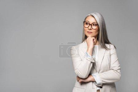 Photo pour Belle réfléchi asiatique femme d'affaires dans lunettes isolé sur gris - image libre de droit