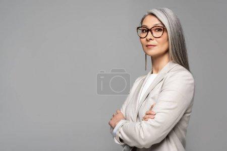 Photo pour Attrayant asiatique femme d'affaires dans des lunettes avec les bras croisés isolé sur gris - image libre de droit
