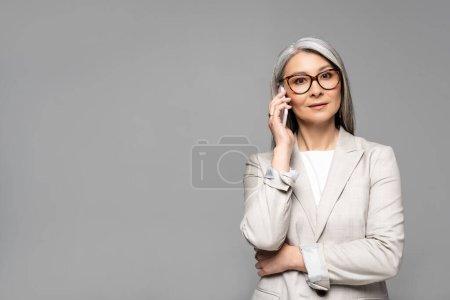 Photo pour Une femme d'affaires asiatique portant des lunettes et des cheveux gris parlant sur un téléphone intelligent isolée sur une - image libre de droit