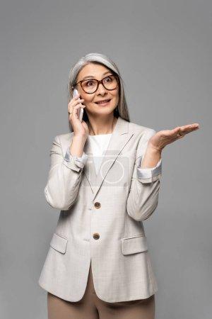 Photo pour Surpris asiatique femme d'affaires dans des lunettes avec des cheveux gris parler sur smartphone isolé sur gris - image libre de droit