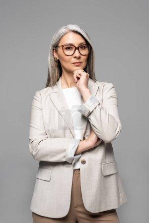Photo pour Réfléchi professionnel asiatique femme d'affaires dans lunettes isolé sur gris - image libre de droit