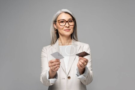 attractive asian businesswoman holding business cards isolated on grey