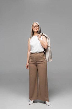 Photo pour Heureux asiatique femme d'affaires dans lunettes debout sur gris - image libre de droit