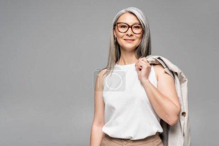 Photo pour Souriant asiatique femme d'affaires dans lunettes isolé sur gris - image libre de droit