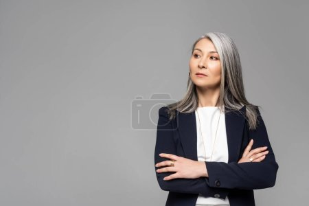 Photo pour Confiant asiatique élégant femme d'affaires avec les cheveux gris et les bras croisés isolé sur gris - image libre de droit