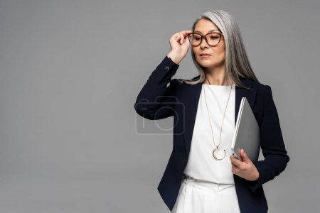 attractive confident asian businesswoman with grey hair holding laptop isolated on grey