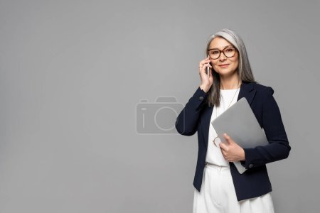 Photo pour Entreprise asiatique femme d'affaires avec des cheveux gris parler sur smartphone et tenant ordinateur portable isolé sur gris - image libre de droit