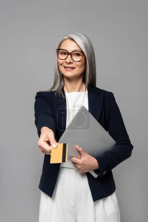 smiling asian businesswoman with grey hair shopping online with credit card and laptop isolated on grey
