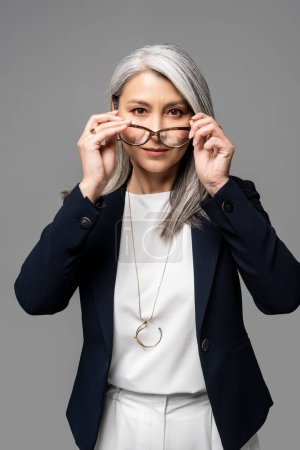Photo for Serious asian businesswoman with grey hair wearing eyeglasses isolated on grey - Royalty Free Image
